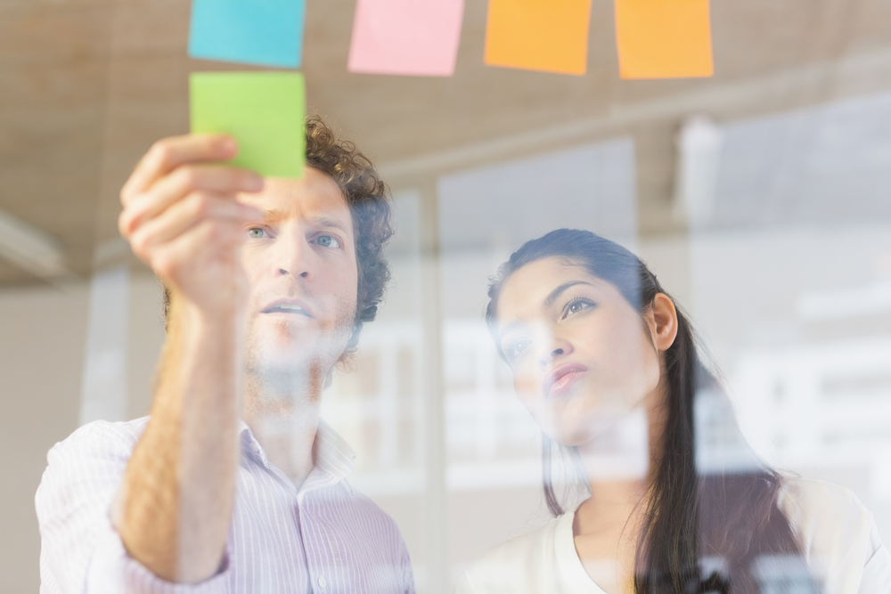 Businessman and businesswoman sticking adhesive notes on glass wall in office
